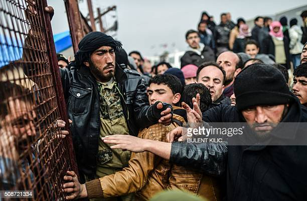 TOPSHOT Refugees push each other as they wait for tents as Syrians fleeing the northern embattled city of Aleppo wait on February 6 2016 in Bab...