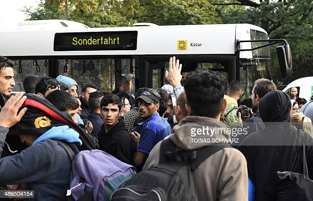 Refugees queue at a public transport bus offering a special ride to a provisional accomodation after they to leave the yard of the Central...