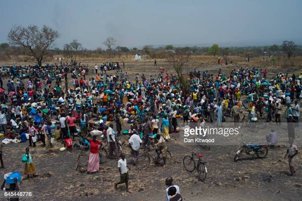 Refugees queue at a World Food Programme food distribution site at a refugee settlement on February 25 2017 in Palorinya Uganda After registering...