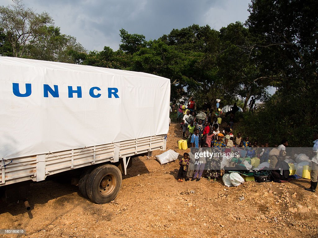 Refugees queue to receive material from the UNHCR (jerrycans, mosquitoe nets, plastic sheets, covers, cooking materials) on March 5, 2013, at Rwamwanja refugee camp, in the Kamwenge district, western Uganda, home to over 35000 refugees, most of them from Democratic Republic of Congo. Four thousand people fled new clashes in eastern Democratic Republic of Congo on February 28, 2013 and crossed the border into neighbouring Uganda, the Red Cross said on March 1. '4,000 refugees crossed into Uganda through Bunagana border,' the Red Cross said.