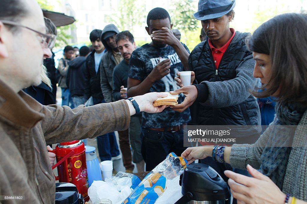 Refugees receive food in a makeshift camp in Paris on May 27, 2016 in Paris. The population of the camp come mostly from Sudan and Afghanistan. / AFP / MATTHIEU