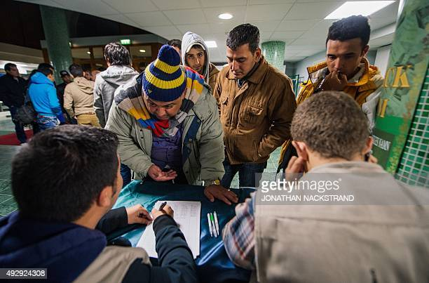 Refugee's register their names as they arrive to Stockholm central mosque on October 15 2015 after many hours bus journey from the southern city of...