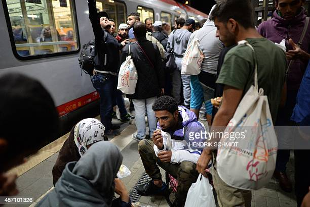 Refugees rest at the main station in Saalfeld eastern Germany on September 5 2015 after arriving by train from Austria Thousands more migrants...