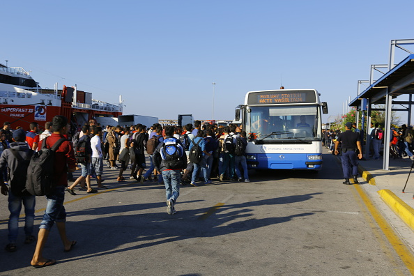 Refugees rush to the bus that will bring them to the Piraeus...
