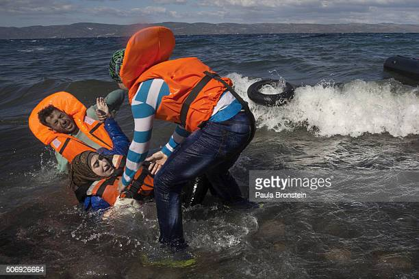 Refugees scramble over the rocks after another raft lands from Turkey on October 282015 in Lesbos Cold weather and rough seas have done little to...