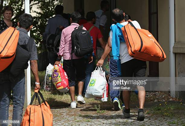 Refugees seeking asylum in Germany arrive at the former 'Lindenhof' hotel that is now serving as refugee accomodation in a residential district on...