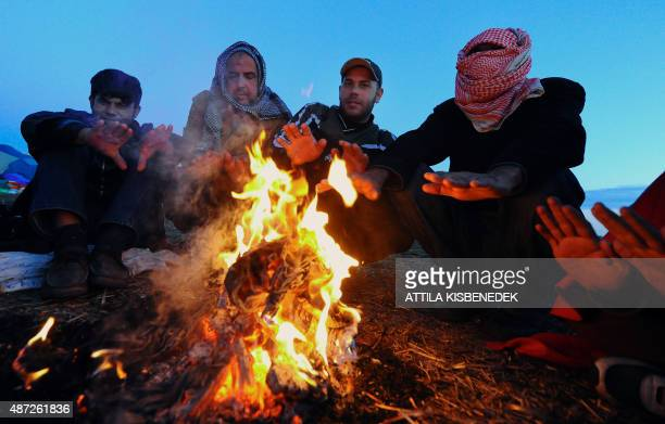 Refugees sit at a bonfire at a migrant collection point as sun rises near Roszke village of the HungarianSerbian border on September 8 2015 Around...