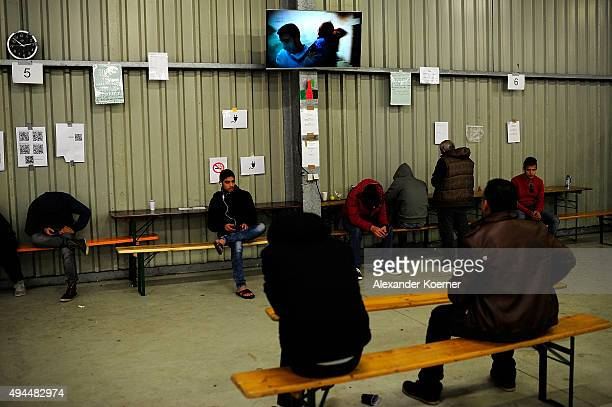 Refugees sit inside a food distribution hall on October 27 2015 in Celle Germany Volunteers have begun to set up weatherresistant accommodation...