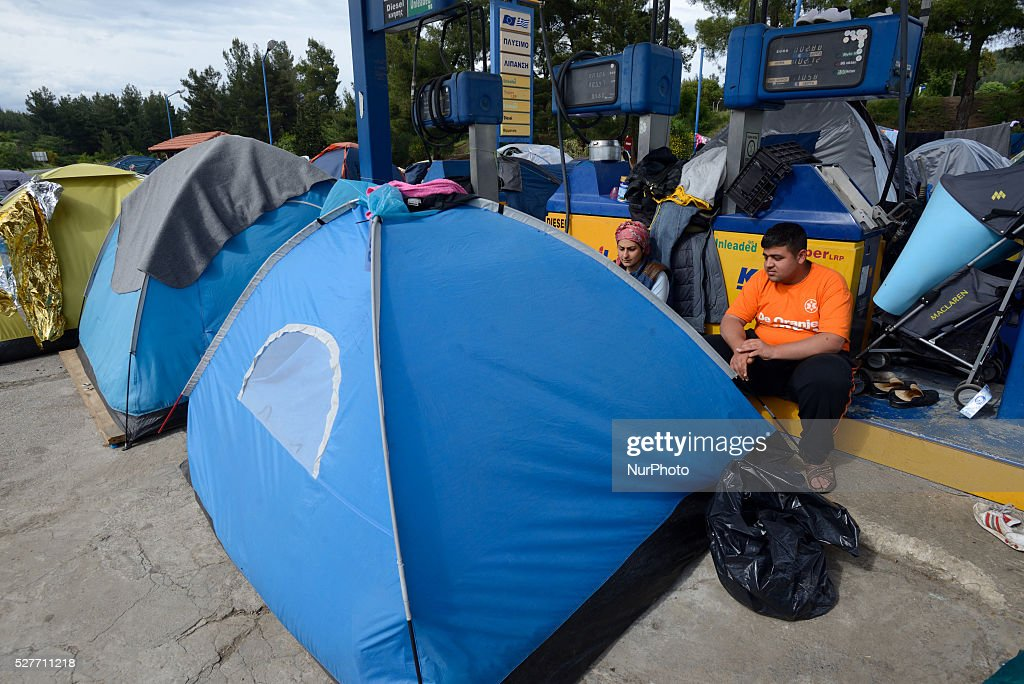 Refugees sit near their tents, located just next to the gas pumps, at the gas station of Hotel Hara, a roadside bungalow in the village of Evzoni, seven kilometres south of the Greek Macedonian border on May 3'rd, 2016. Hotel Hara, the sorroundings and the attached gas station are fully occupied with refugee tents.