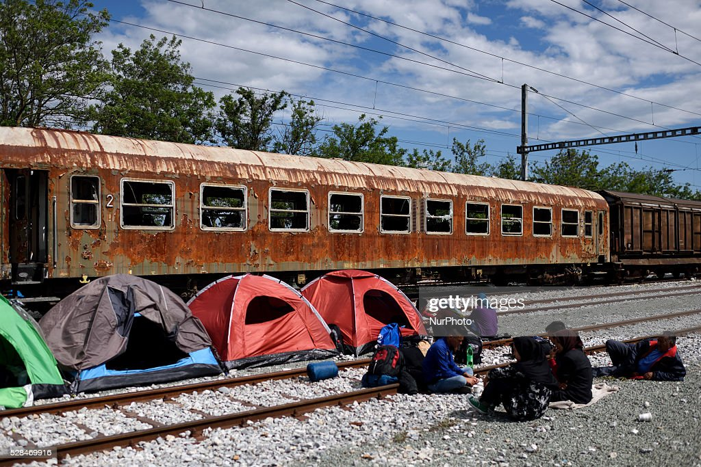 Refugees sit near their tents on the rails of the abandoned train station at Idomeni refugee camp on May 5'th, 2016. Thousands of migrants are still located in the makeshift refugee camp, located at the Greek Macedonian border, waiting for the border to re-open.