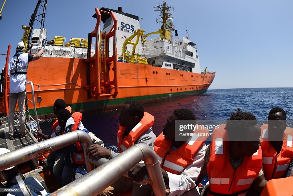 Refugees sit on a boat during a rescue operation of migrants and refugees at sea of the 'Aquarius', a former North Atlantic fisheries protection ship now used by humanitarians SOS Mediterranee and Medecins Sans Frontieres (Doctors without Borders), on May 24, 2016 in the Mediterranean sea in front of the Libyan coast. / AFP / GABRIEL