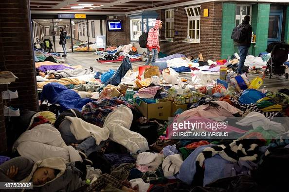 Refugees sleep amongst donations at the train station in Flensburg northern Germany on September 10 2015 Train transport has resumed after Danish...