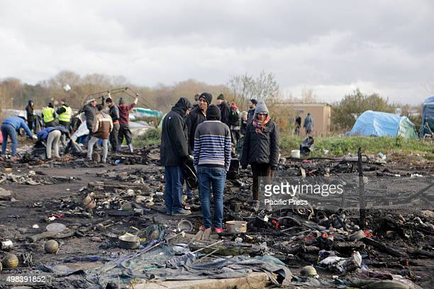 Refugees stand among the burnt rubble at the new Jungle refugee camp 3 people have been hospitalized and over 50 huts and tents have been destroyed...