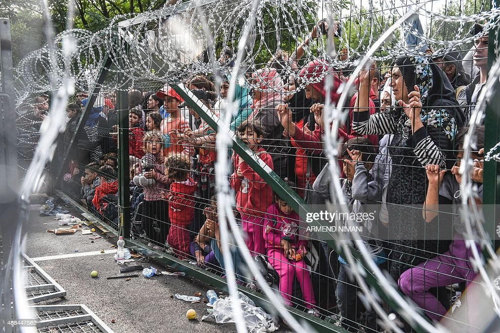 Refugees stand behind a fence at the Hungarian border with Serbia near the town of Horgos on September 16 2015 Europe's 20year passportfree Schengen...