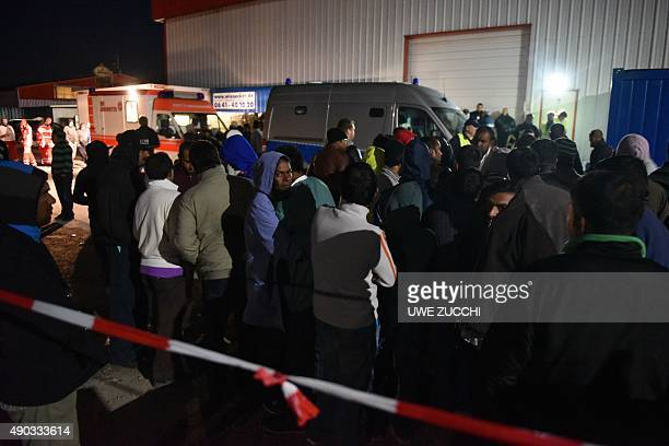 Refugees stand by rescuers and police officers outside a migrants shelter in Calden near Kassel on September 27 2015 where clashes erupted between...