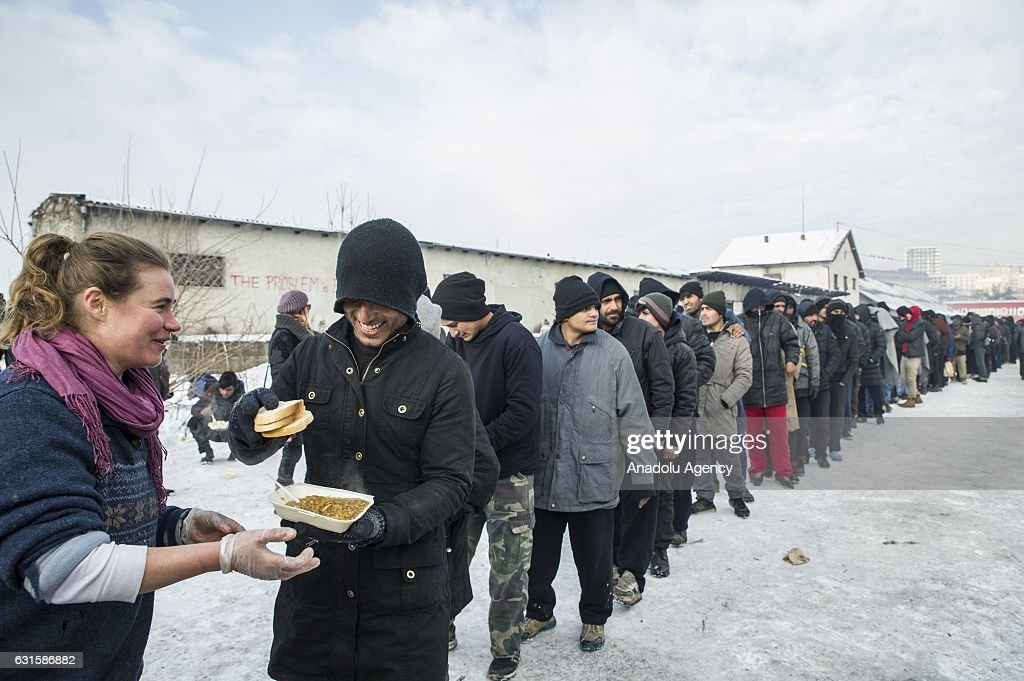 Refugees stand in line for food distributed by Hot Food Idomeni outside a derelict warehouse where they took shelter in Belgrade, Serbia on January 12, 2017. Hot Food Idomeni is a non-political group providing humanitarian aid and collaboration and coordination with NGOs and organisations, including MSF, UNHCR, etc. Despite the help of local and international organisations, the situation in the warehouses have been very precarious for months, waiting on borders to open. Refugees mostly coming from Afghanistan, Pakistan, Iraq and Syria,sleep on the warehouse floor, wrapped up in blankets to keep out the bitter cold.