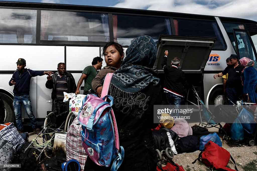 Refugees stand near a bus as they wait to be transferred to a hospitality centre during a police operation at a refugee camp at the border between Greece and Former Yugoslav Republic of Macedonia (FYROM), near the village of Idomeni, northern Greece,on May 25, 2016. Greek police restarted an operation to move migrants out of Idomeni, the squalid tent city where thousands fleeing war and poverty have lived for months. The migrants and refugees on May 24 were bussed to newly opened camps near Greece's second city Thessaloniki, about 80 kilometres (50 miles) to the south. / AFP / POOL / Yannis KOLESIDIS