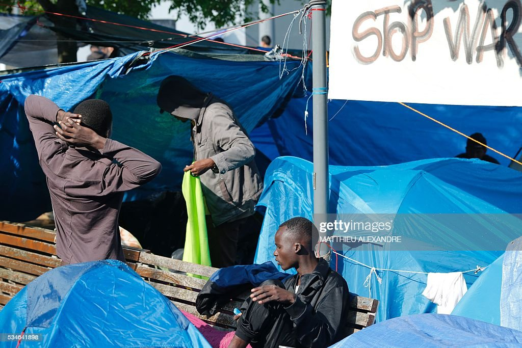 Refugees stand next to their tents in a makeshift camp in Paris on May 27, 2016. The population of the camp come mostly from Sudan and Afghanistan. / AFP / MATTHIEU