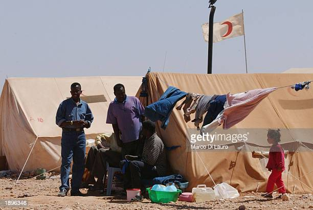 Refugees stand outside of their tent together April 4 2003 at the International Federation of Red Cross and Crescent Society refugee camp some 75 km...