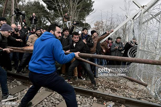 TOPSHOT Refugees try to break into the GreekMacedonian borders during their protest demanding the opening of the borders near the village of Idomeni...