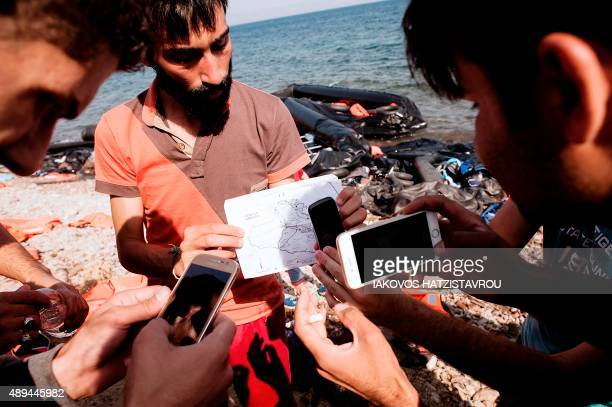 Refugees use mobile phones to take pictures of a map upon their arrival on Eftalou beach west of the port of Mytilene on the Greek island of Lesbos...