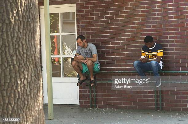 Refugees use their mobile phones at a temporary home providing assistance for refugees on August 6 2015 in the Gatow district of Berlin Germany Since...