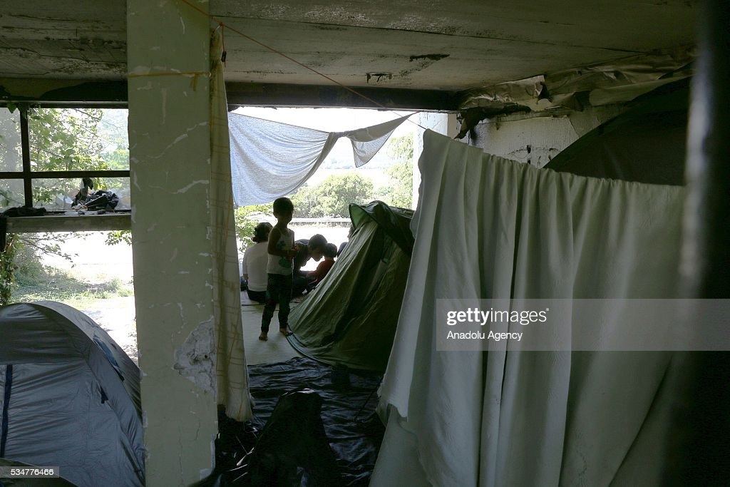 Refugees wait at abandoned buildings near a gas station at Evzonoi, Greece May 27, 2016 after they were evacuated from the tents which were located in Greece-Macedonia border town of Idomeni. However refugees were evacuated from Idomeni to be re-settled at proper camps, they refuse to go other camps as they still want the cross the border.