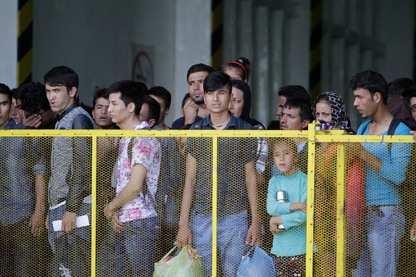Refugees wait behind rails on board the ferry, before they...
