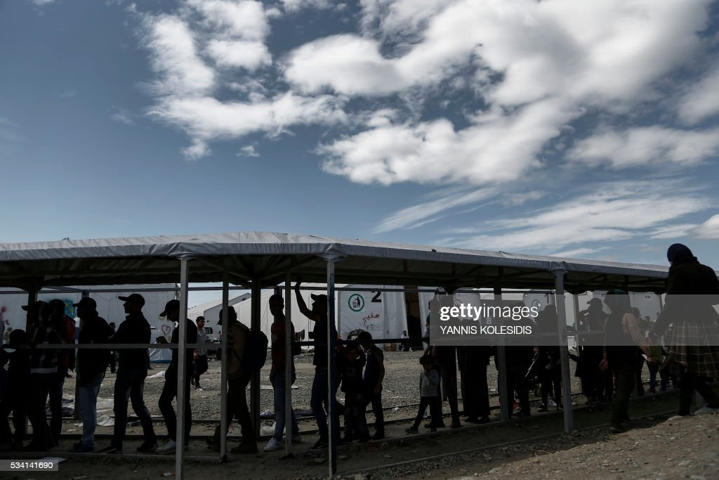 Refugees wait for food distribution during a police operation to clear a refugee and migrant camp at the border between Greece and Macedonia near the village of Idomeni, northern Greece on May 25, 2016. Greek police restarted an operation to move migrants out of Idomeni, the squalid tent city where thousands fleeing war and poverty have lived for months. The migrants and refugees on May 24 were bussed to newly opened camps near Greece's second city Thessaloniki, about 80 kilometres (50 miles) to the south. / AFP / POOL / Yannis KOLESIDIS