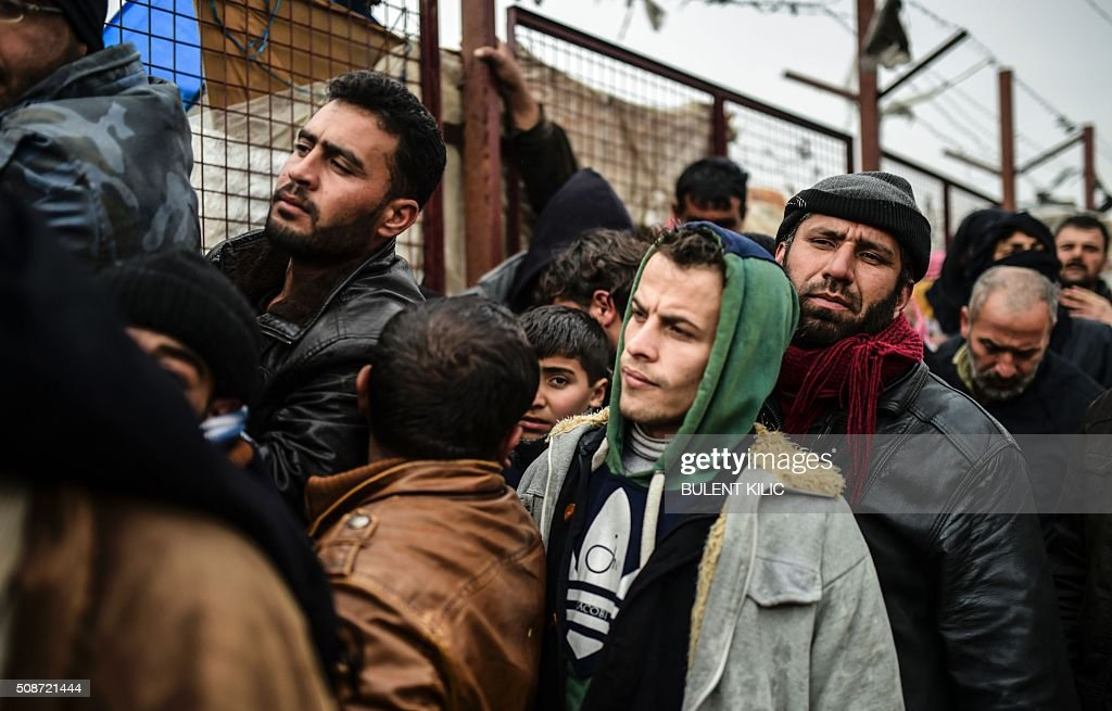 Refugees wait for tents as Syrians fleeing the northern embattled city of Aleppo wait on February 6, 2016 in Bab-Al Salam, near the city of Azaz, northern Syria, near the Turkish border crossing. Thousands of Syrians were braving cold and rain at the Turkish border Saturday after fleeing a Russian-backed regime offensive on Aleppo that threatens a fresh humanitarian disaster in the country's second city. Around 40,000 civilians have fled their homes over the regime offensive, according to the Syrian Observatory for Human Rights monitor. / AFP / BULENT KILIC