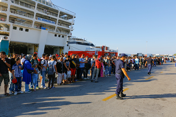 Refugees wait for the bus that will bring them from the...
