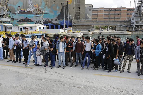Refugees wait for the busses to arrive, that will bring them...