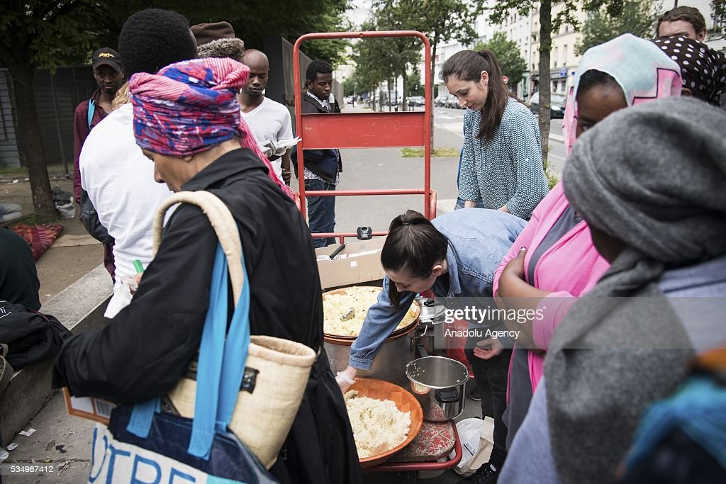 Refugees wait in a queue for food distribution as they live in harsh conditions at a makeshift camp set at the Jardin d'Eole in Paris on May 28, 2016.