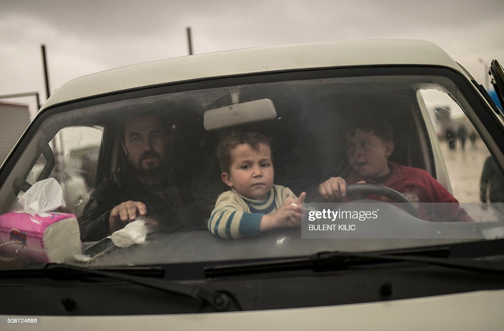 Refugees wait inside a car near the Turkish border crossing gate as Syrians fleeing the northern embattled city of Aleppo wait on February 6, 2016 in Bab-Al Salam, near the city of Azaz, northern Syria. Thousands of Syrians were braving cold and rain at the Turkish border Saturday after fleeing a Russian-backed regime offensive on Aleppo that threatens a fresh humanitarian disaster in the country's second city. Around 40,000 civilians have fled their homes over the regime offensive, according to the Syrian Observatory for Human Rights monitor. / AFP / BULENT KILIC