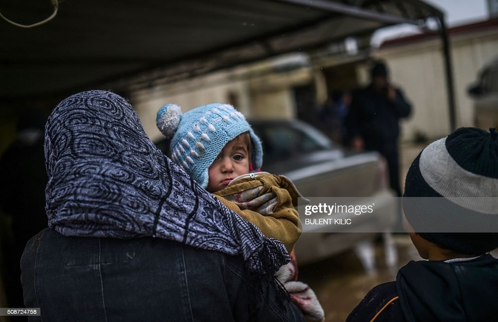 Refugees wait near the Turkish border crossing gate as Syrians fleeing the northern embattled city of Aleppo wait on February 6, 2016 in Bab-Al Salam, near the city of Azaz, northern Syria. Thousands of Syrians were braving cold and rain at the Turkish border Saturday after fleeing a Russian-backed regime offensive on Aleppo that threatens a fresh humanitarian disaster in the country's second city. Around 40,000 civilians have fled their homes over the regime offensive, according to the Syrian Observatory for Human Rights monitor. / AFP / BULENT KILIC