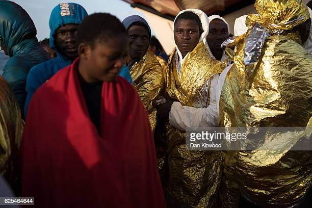 Refugees wait to disembark the MOAS vessel 'Topaz Responder' on November 24 2016 in Vibo Valentia Italy The MOAS team worked through the night of the...