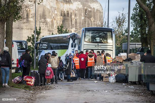 Refugees wait with their luggages as they walk to climb into a bus after leaving the 'Jules Ferry' center reception in Calais on November 3 2016 Over...