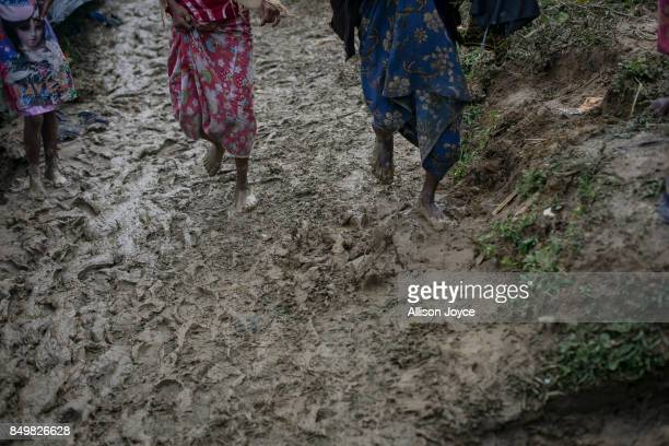 COX'S BAZAR BANGLADESH SEPTEMBER 19 Refugees walk a muddy road in the Falungkhali Rohingya refugee camp on September 19 2017 in Cox's Bazar...