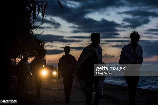 Refugees walk during sunset as they arrived with other refugees on the shores of the Greek island of Lesbos after crossing the Aegean sea from Turkey...