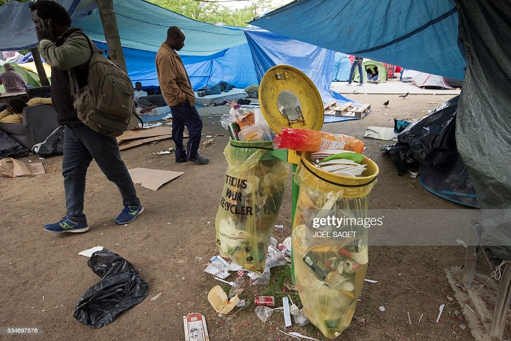 Refugees walk in a makeshift camp in Paris on May 27, 2016. SAGET
