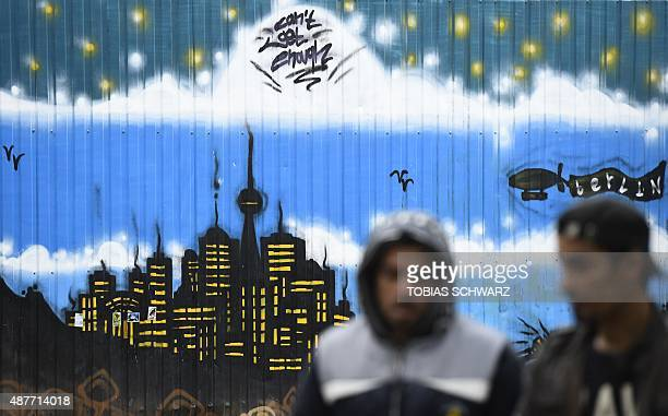 Refugees walk past a wall painting featuring Berlin's skyline at a temporary refugee home in Berlin's Spandau district on September 11 2015 The...