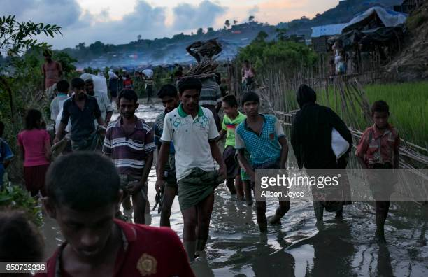 COX'S BAZAR BANGLADESH SEPTEMBER 21 Refugees walk through a muddy path in the Unchiprang Rohingya refugee camp on September 21 2017 in Cox's Bazar...