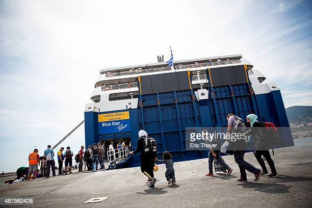 Refugees walk toward a ferry at the port in Mytilini on September 9 2015 in Lesbos Greece Greece has been overwhelmed this year by record numbers of...