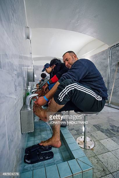 Refugee's wash their feet and refresh at Stockholm central mosque bathroom on October 15 2015 after many hours bus journey from the southern city of...