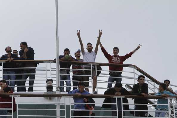 Refugees wave from the railing of the El. Venizelos while it...
