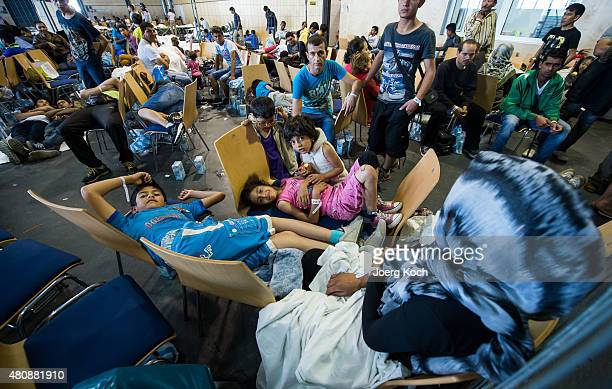 Refugees who arrived in Germany by crossing the nearby Austrian border wait in the waiting zone at the XPoint Halle initial registration center of...