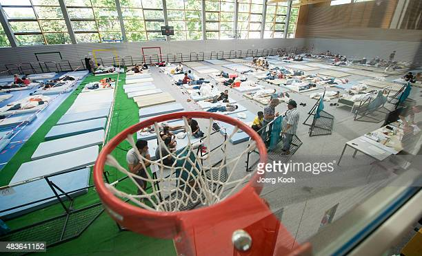 Refugees who arrived in Germany by crossing the nearby Austrian border wait in a rest area placed in a sports hall of an initial registration center...