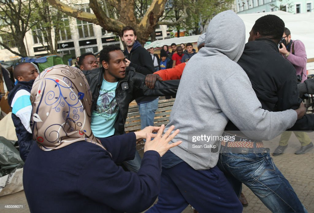 Refugees who disagreed over a deal with city authorities to move to a new shelter scuffle as nearby huts were torn down at a temporary, city-tolerated refugee camp at Oranienplatz in Kreuzberg district on April 8, 2014 in Berlin, Germany. Refugees, many of them from Africa who came to Germany via Lampedusa, began dismantling their shelters today after many of them agreed to a deal with city authorities to move to a renovated hostel. Not all of the several hundred refugees, some of whom have been living at the Oranienplatz camp almost a year, have agreed to the deal, and while some said they will go elsewhere, some insist they will stay, despite a city order to vacate.