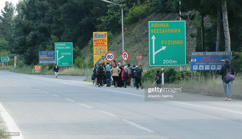 Refugees who do not want to be bussed to another camp with their families leave on foot the Idomeni camp as Greek police evacuate the makeshift refugee camp at the Greek-Macedonian border near the northern Greek village of Idomeni on May 25, 2016.