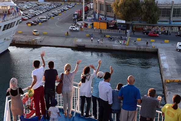 Refugees who got their asylum requests processed following the EU-Turkey deal, wave as they leave the island of Lesbos towards the port of Piraeus on July 21, 2016. When a sea of humanity landed on...
